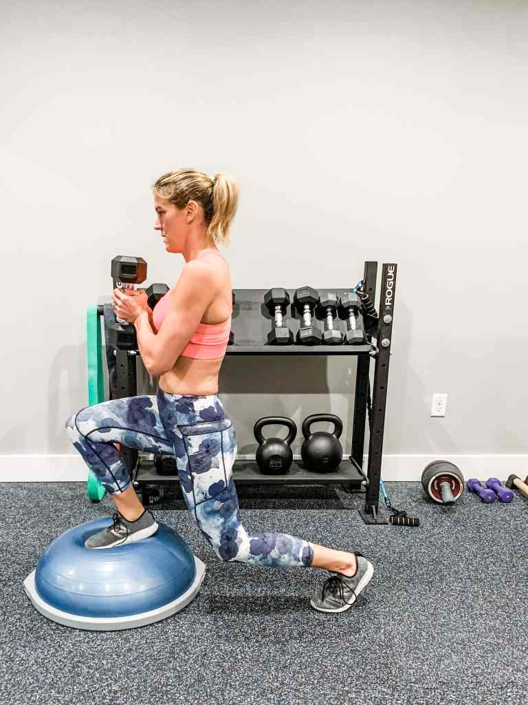 Completing a backward lunge on a bosu ball