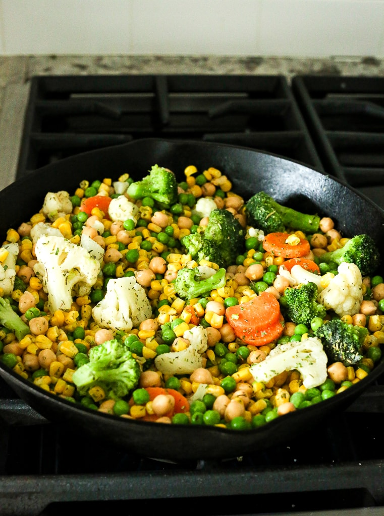 vegetables and chickpeas in a cast iron skillet on a stovetop