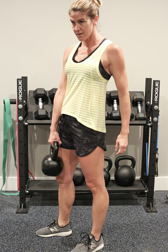 a woman standing in front of a weight rack holding a kettlebell