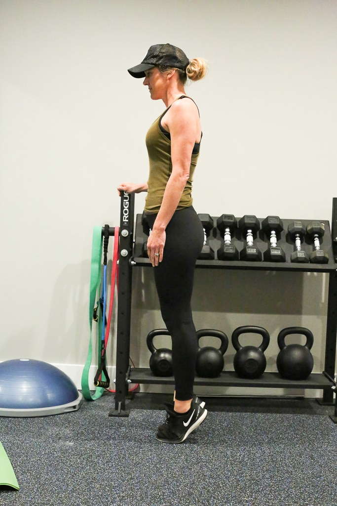 a woman completing calf raises with no weights