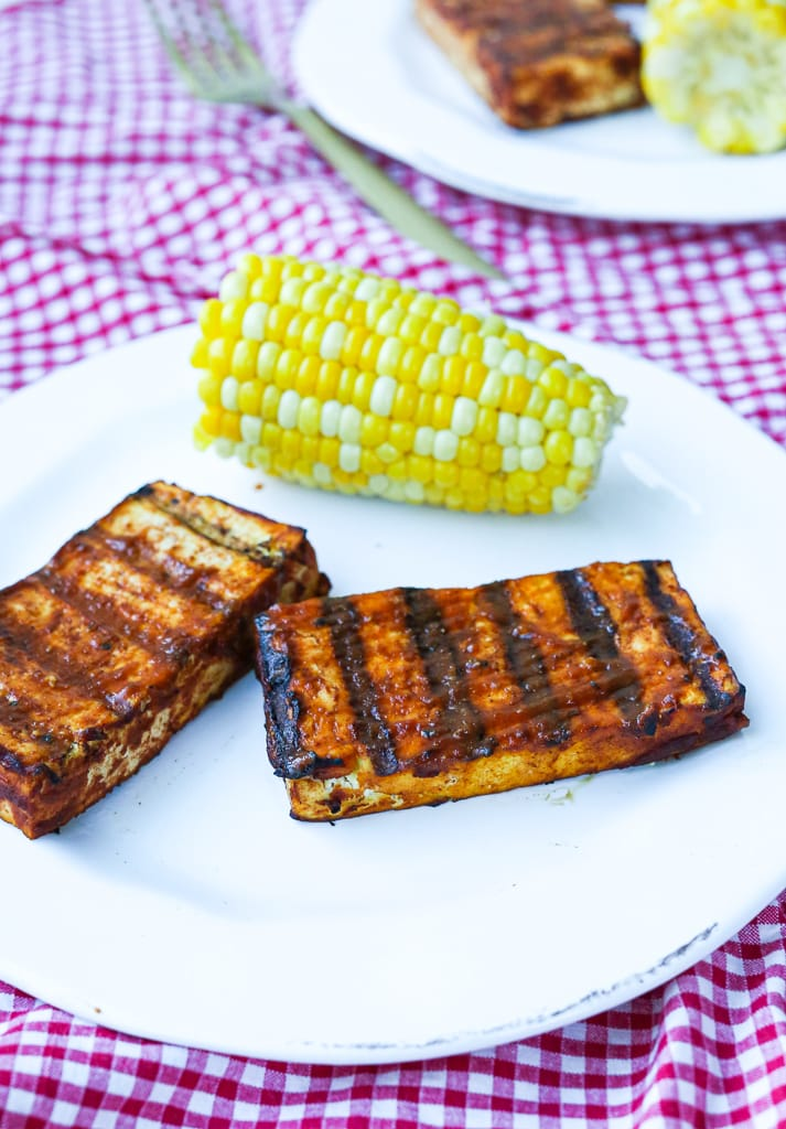 Two pieces of Grilled barbecue Tofu on a plate with corn on the cob and a red checked tablecloth