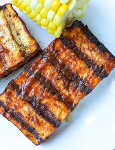 On overhead shot of grilled tofu with barbecue sauce and a little bit of corn on the cob showing on a white plate