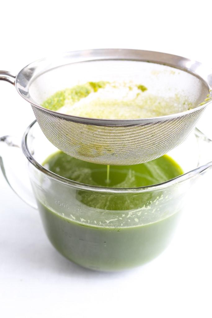 a fine mesh sieve straining fresh green juice