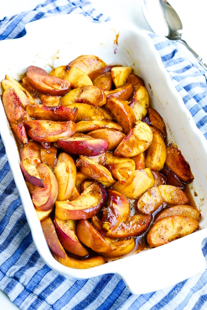 a white pan with baked peaches with a blue napkin underneath