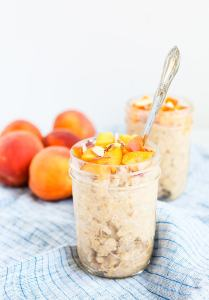 2 mason jars filled with overnight oats topped with peaches and almonds on a blue and white striped napkin and fresh peaches in the background