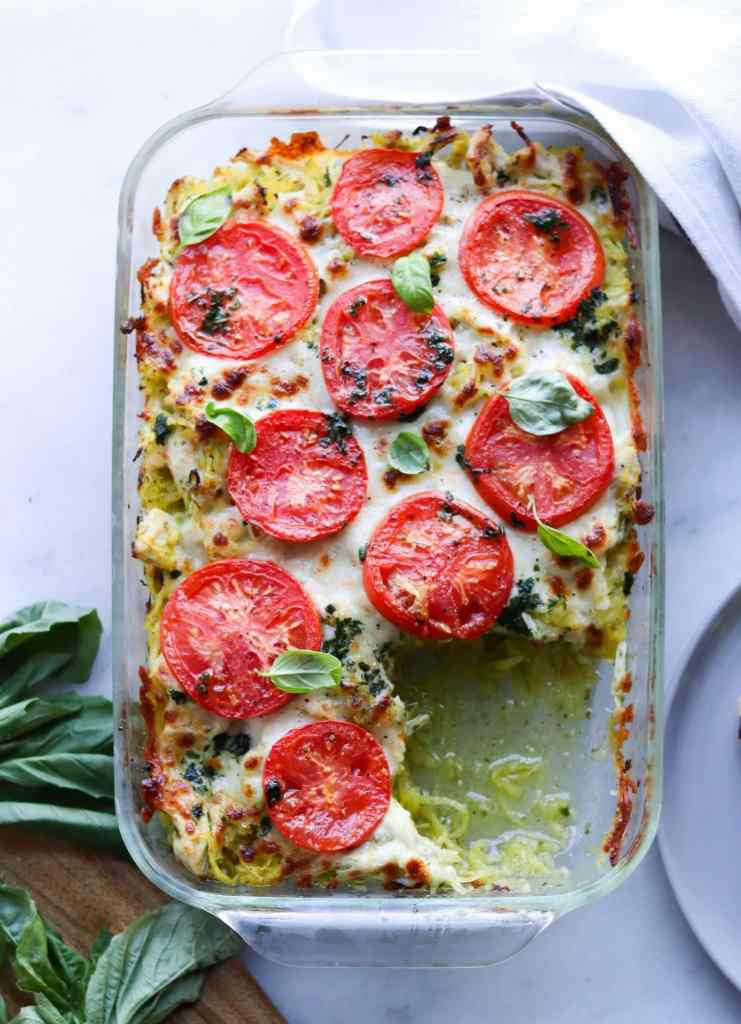 overhead shot of a baked casserole with tomatoes, cheese, and basil in a glass dish with pieces of fresh basil Ono the side