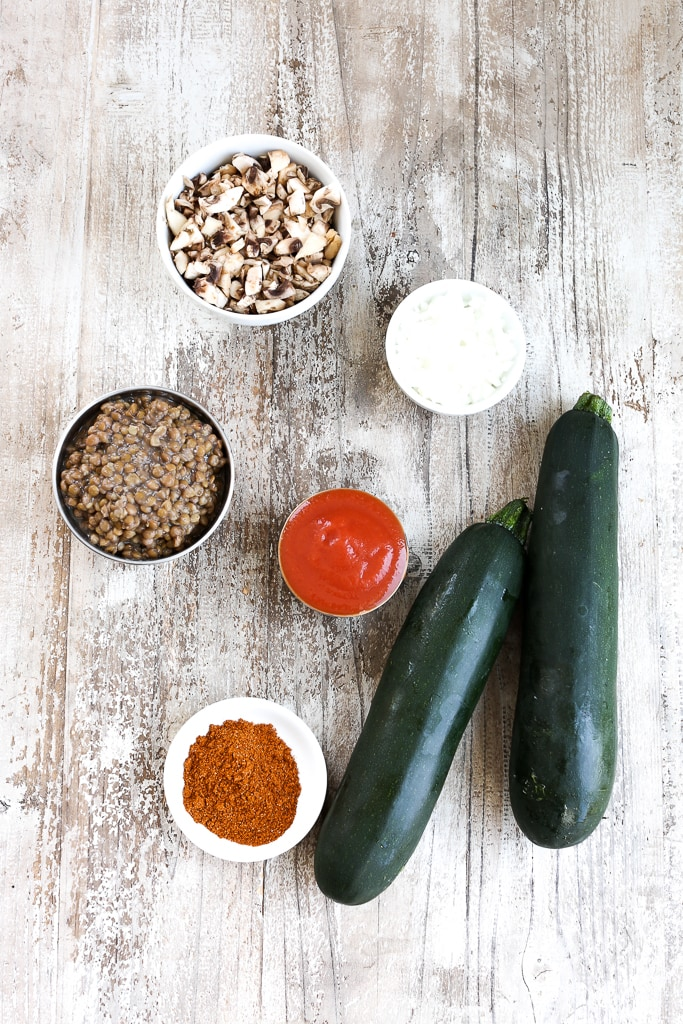 recipe ingredients on a board--zucchini, lentils, onion, tomato sauce, taco seasoning