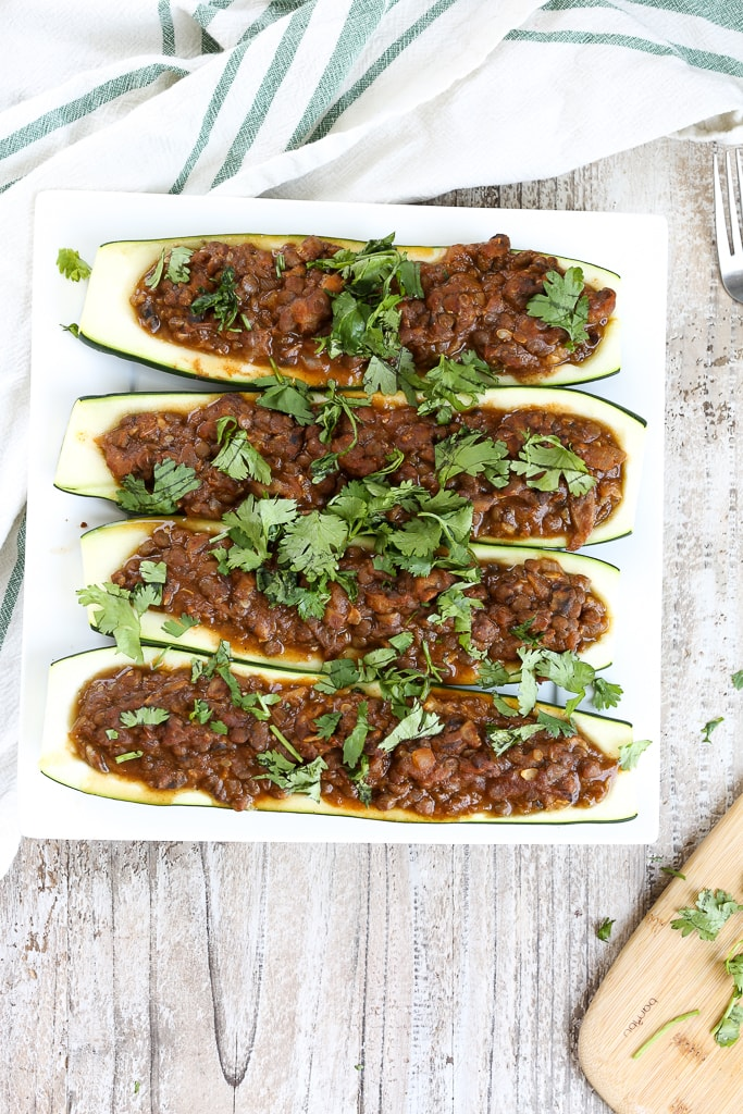 an overhead shot of taco stuffed zucchini boats topped with cilantro on a white plate
