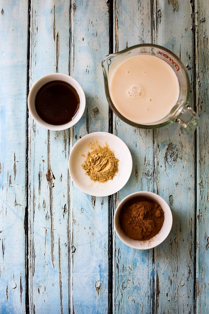 overhead shot of recipe ingredients, almond milk, maca root powder, cocoa powder, and maple syrup