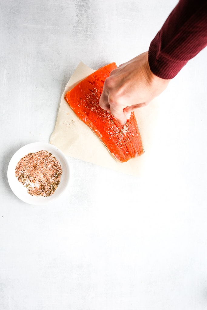 a hand adding seasoning to a raw salmon filet