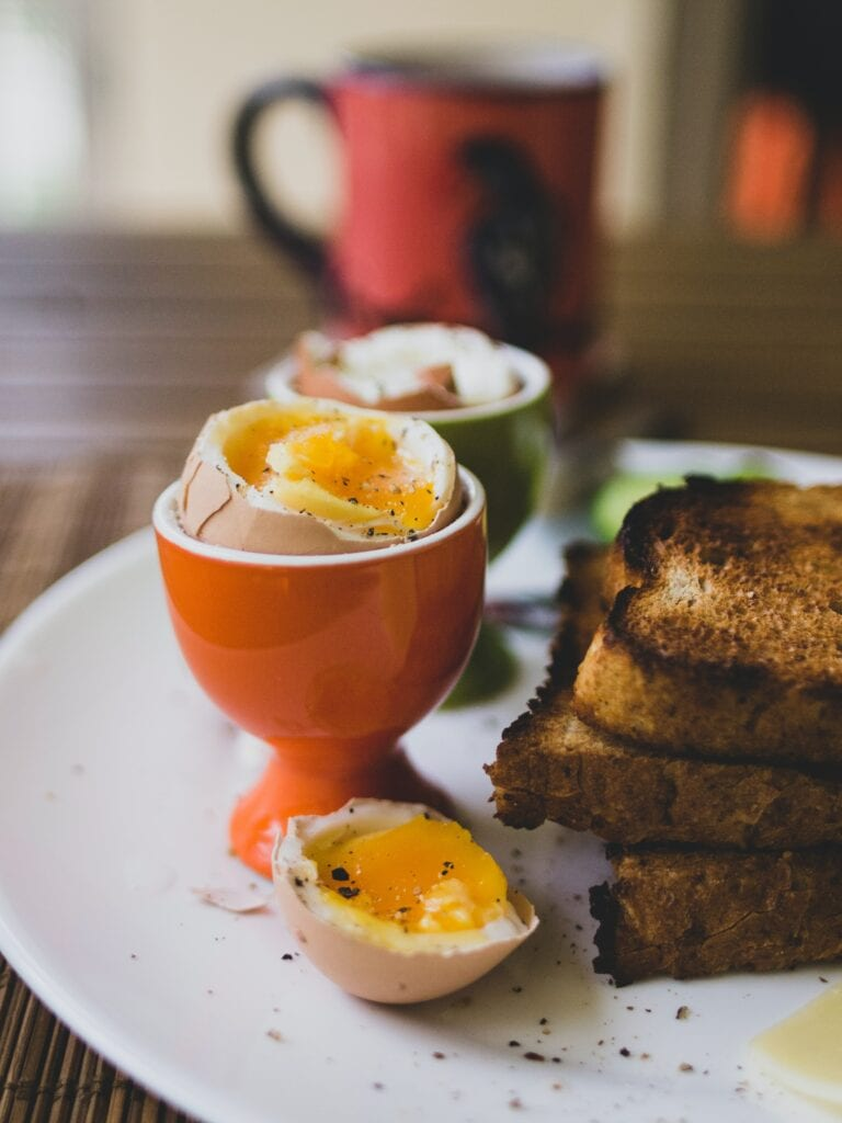 a soft boiled egg in a stand with toast