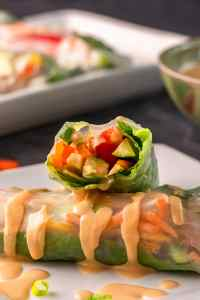 Vegan Spring Rolls Recipe one cut in half stacked on another with peanut sauce