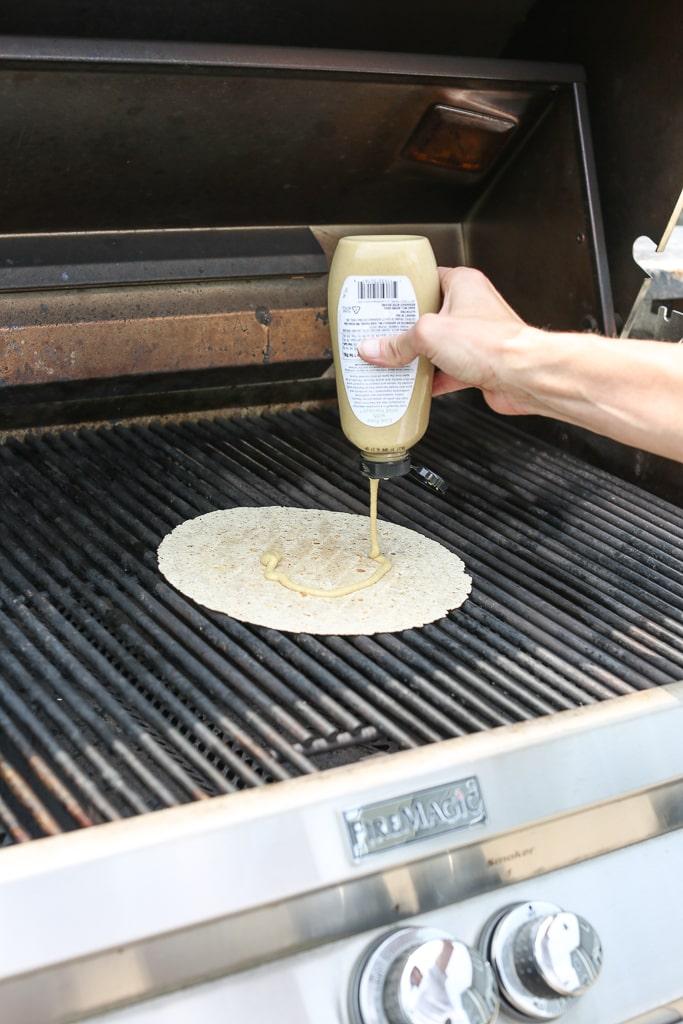 adding mustard to the quesadilla