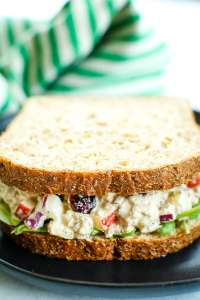 apple cranberry tuna salad on bread with a green and white striped napkin