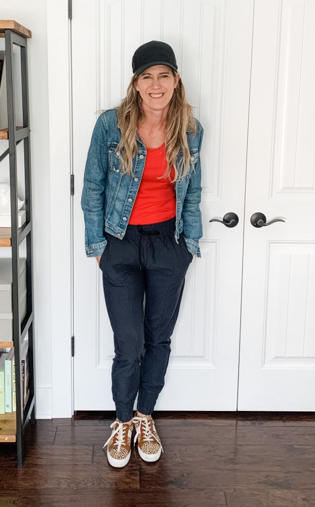 black joggers with a red top and denim jacket
