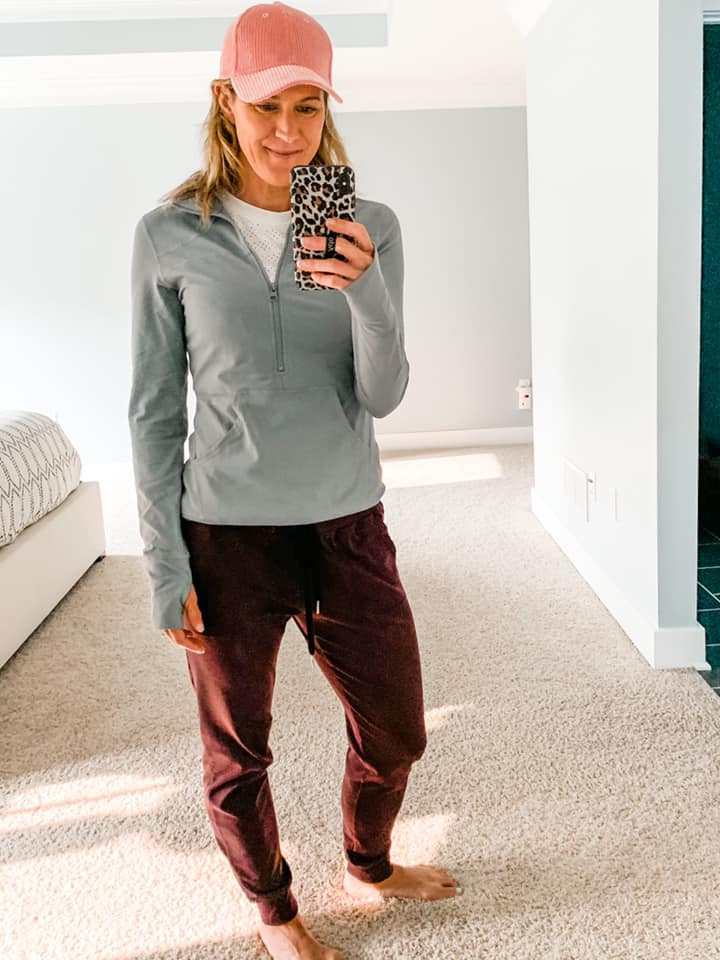a woman in plum colored joggers, gray 1/2 zip pullover, and a pink hat