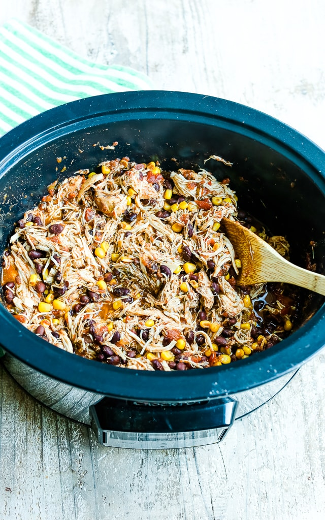 Crockpot Chicken Tacos Recipe stirring the ingredients together in the slow cooker