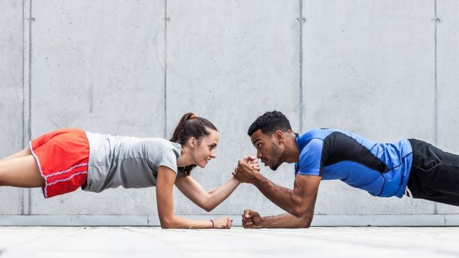 Man and woman planking in workout clothing