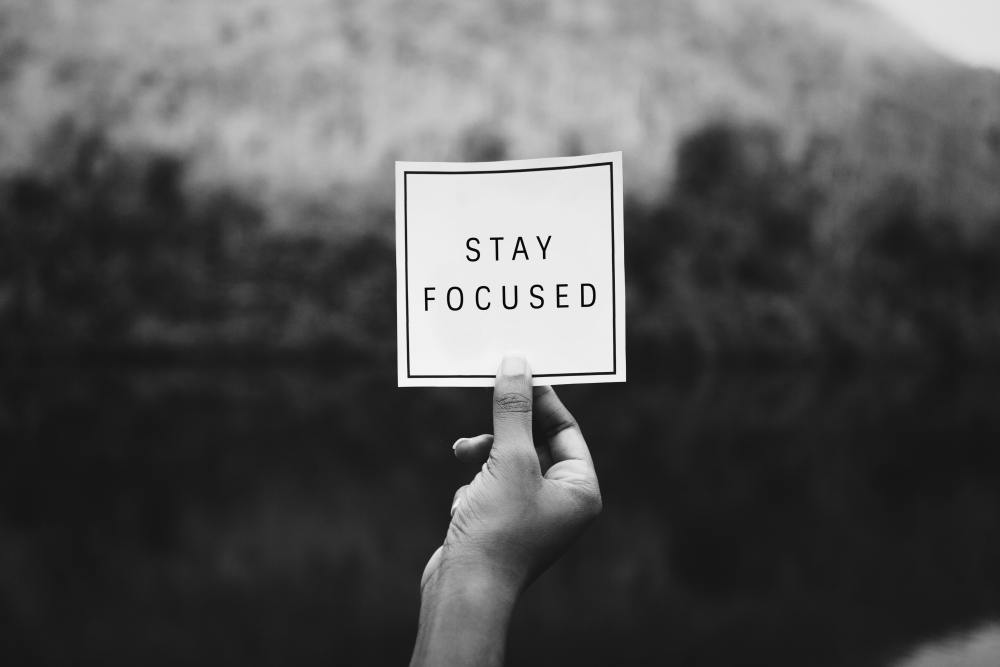 Hand Holding a Note Card that Says Stay Focused- Motivated