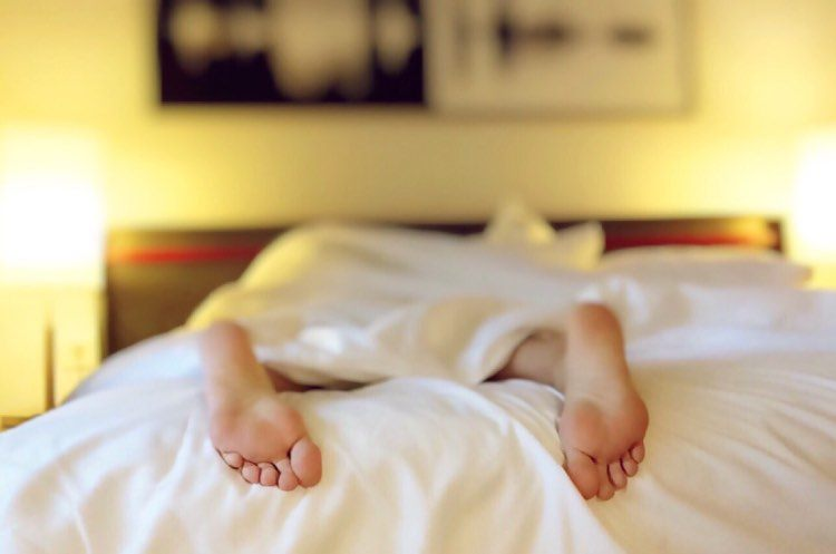 Person With Feet Hanging Off The End Of The Bed
