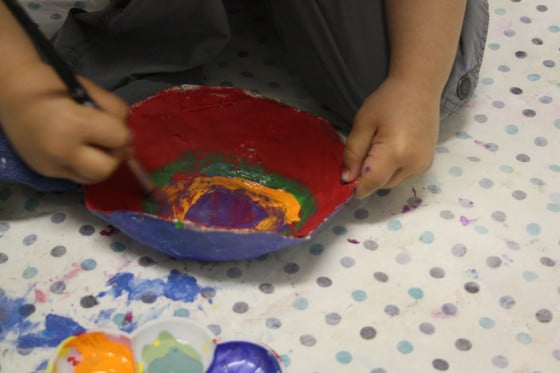 Toddler painting paper mache bowl