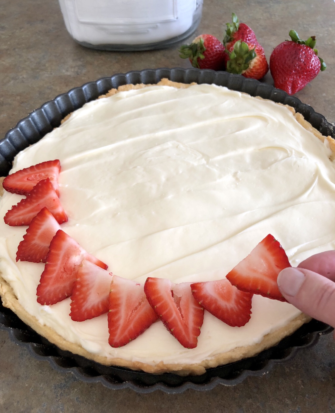 Layer the strawberry slices on top of the cream cheese filling. #tart #fruittart #dessert #summerdessert #summertart