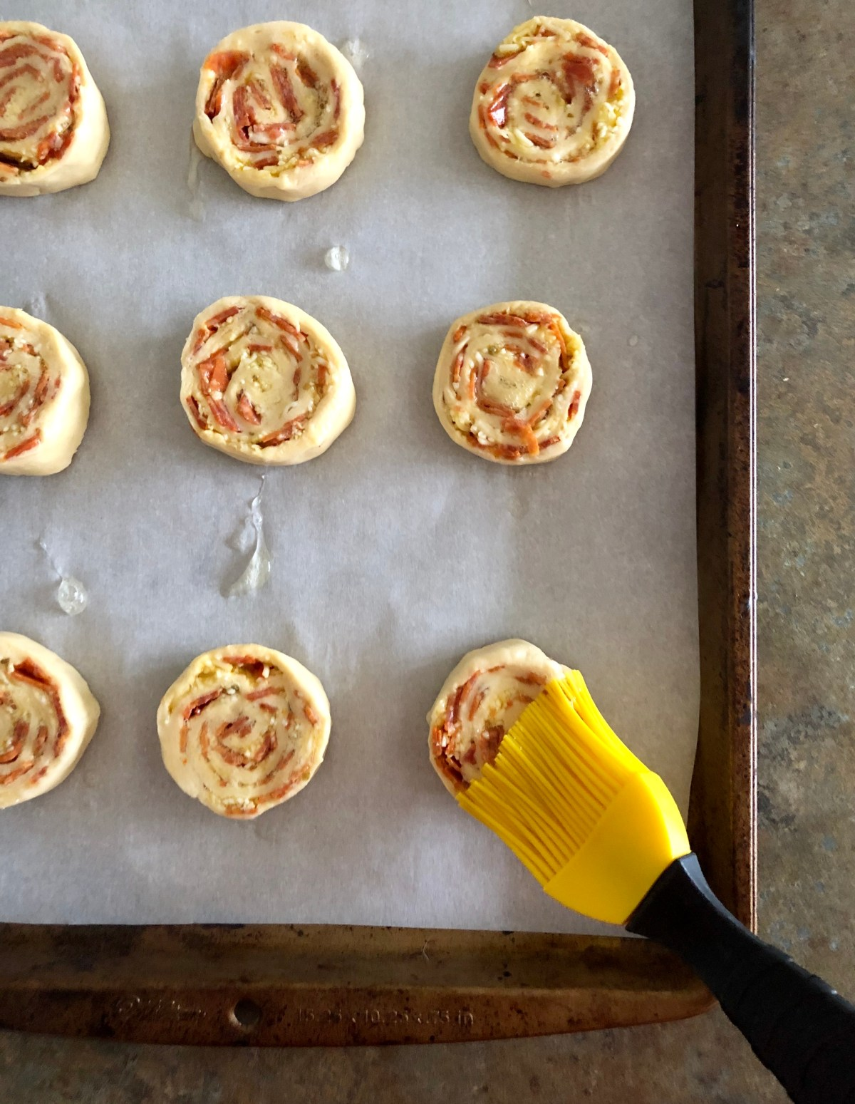 Pizza Pinwheel dough slices place on a baking sheet lined with parchment paper.