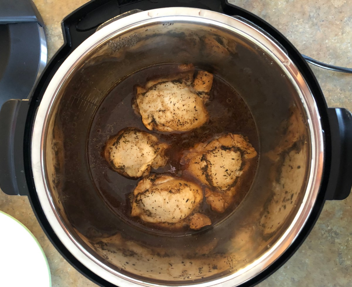 Chicken Thighs in the pressure cooker pot after they've finished cooking.