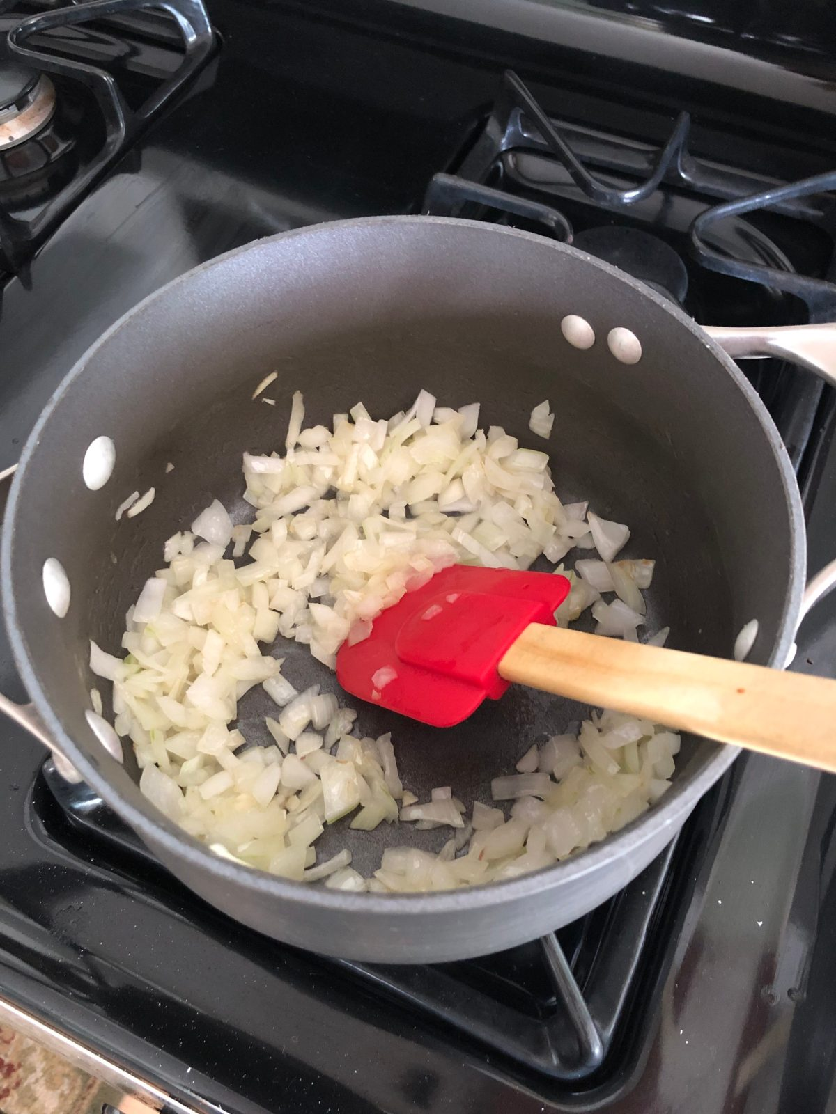 Chopped onions cooking in a sauce pan on the stove top.