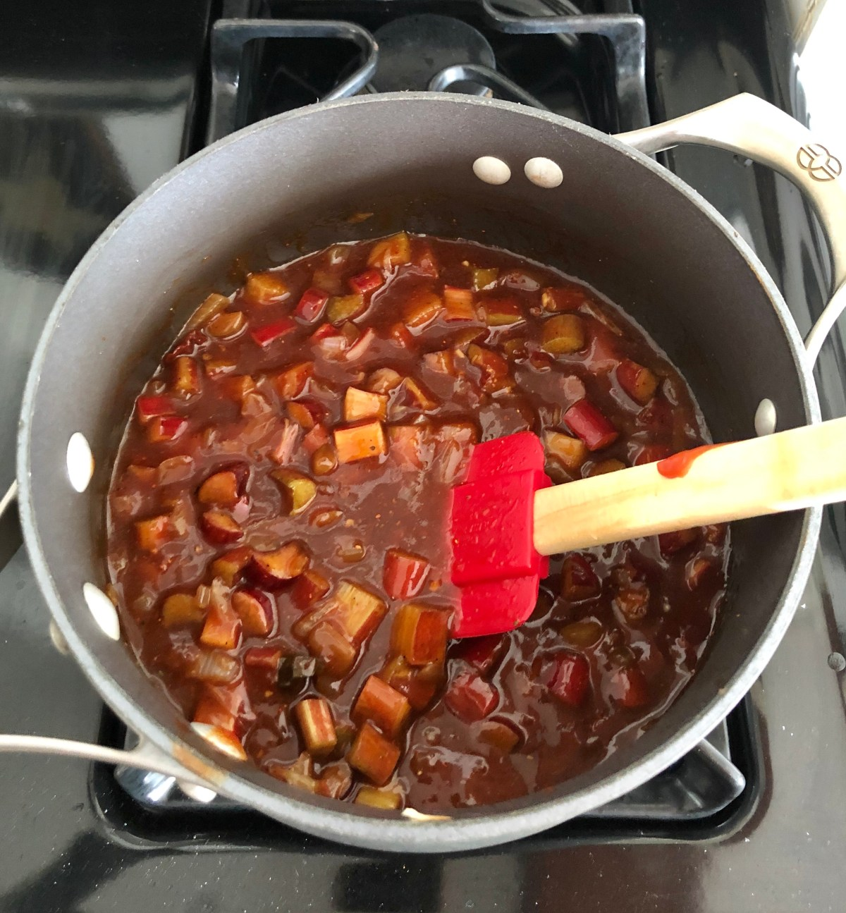 Sliced rhubarb, ketchup, water, apricot preserves, apple cider vinegar, molasses, Dijon mustard, chipotle pepper, 1 teaspoon barbecue seasoning, 1/4 teaspoon salt and 1/4 teaspoon pepper are added to the sauce pan.