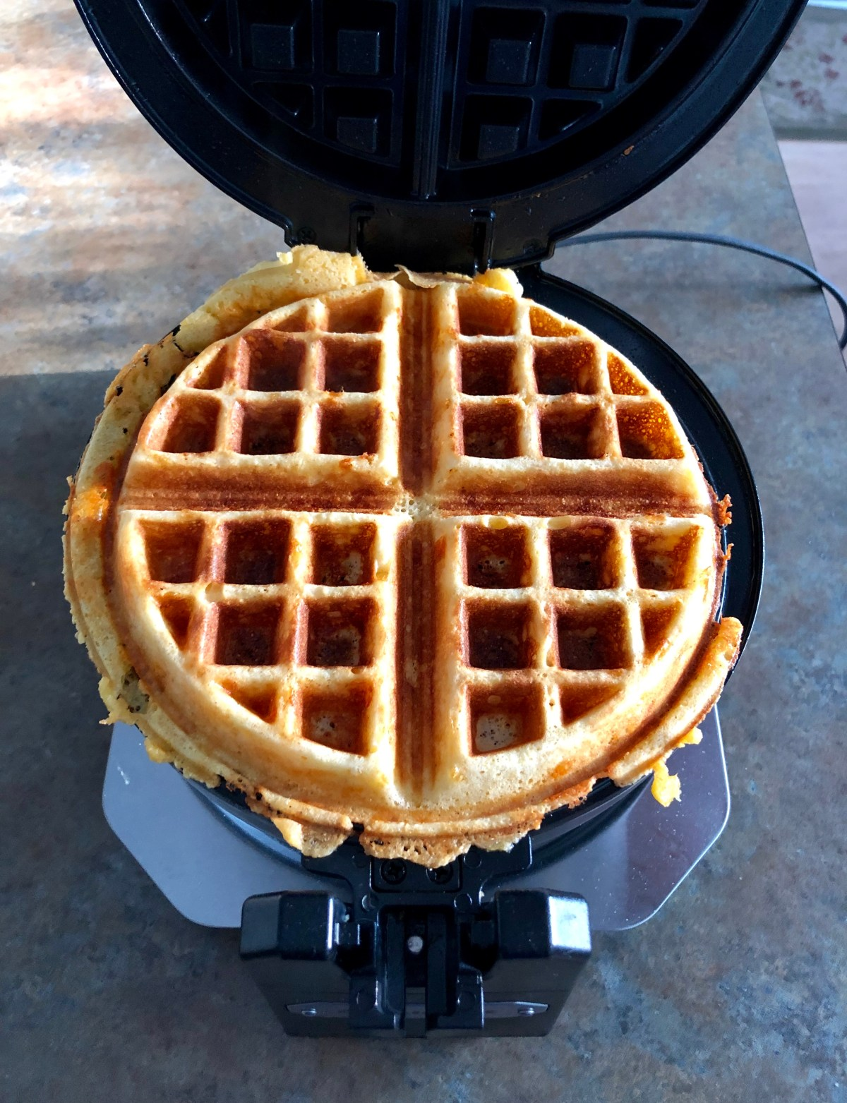 Freshly cooked waffle sitting in a round waffle maker.