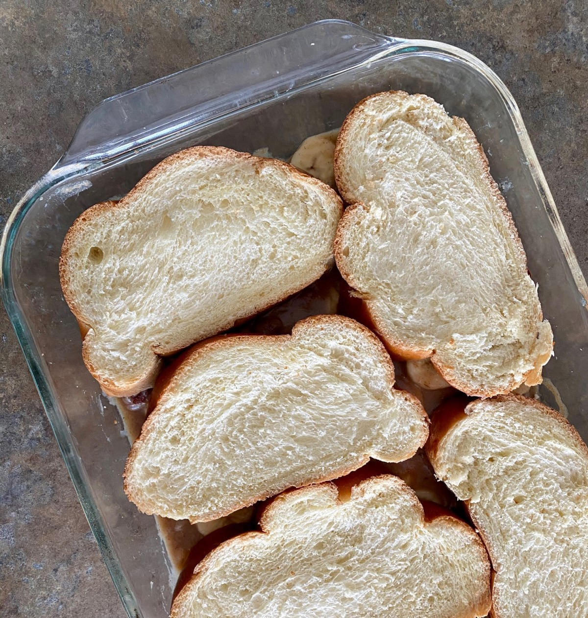 The banana mixture is added to a 13X9-inch casserole dish and then topped with Challah bread slices. #bananasfosterfrenchtoast #bananasfosterrecipes #breaskfastrecipes #neworleansrecipes #frenchtoastcasserole #fattuesdaybreakfast
