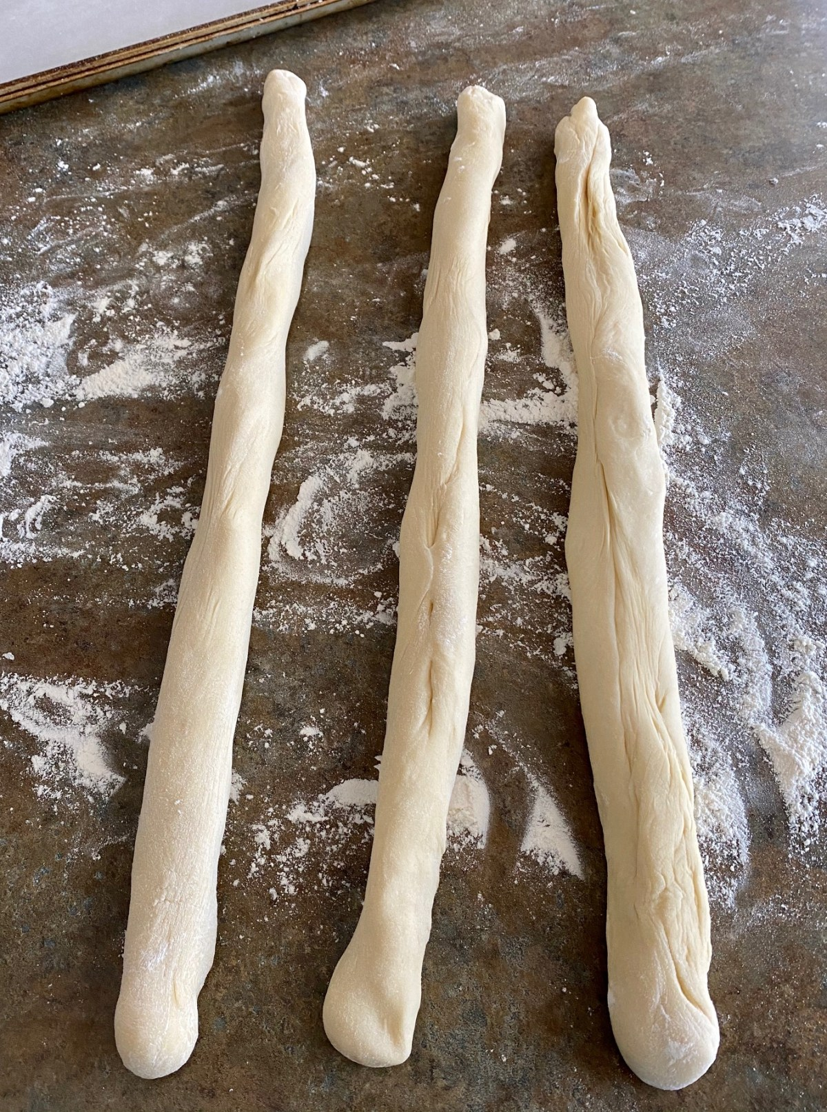 Everything Bread dough shaped into three 20-inch ropes. #everythingbread #easybreadrecipes #homemadebread #breadfromscratch #braidedbread