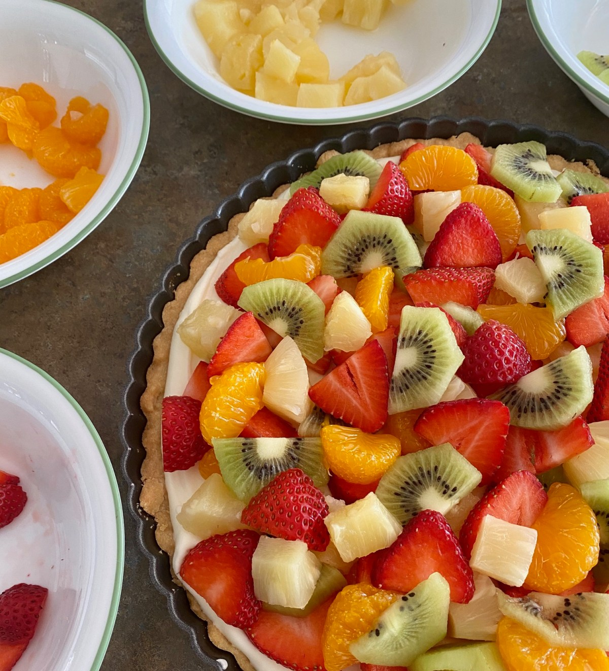 Mandarin oranges, pineapple chunks, kiwi and strawberries are layered on top of the tart filling. #fruittart #dessertideas #dessertrecipes #brunchdessert #holidaydessert #partydessert #backtoschoolrecipes