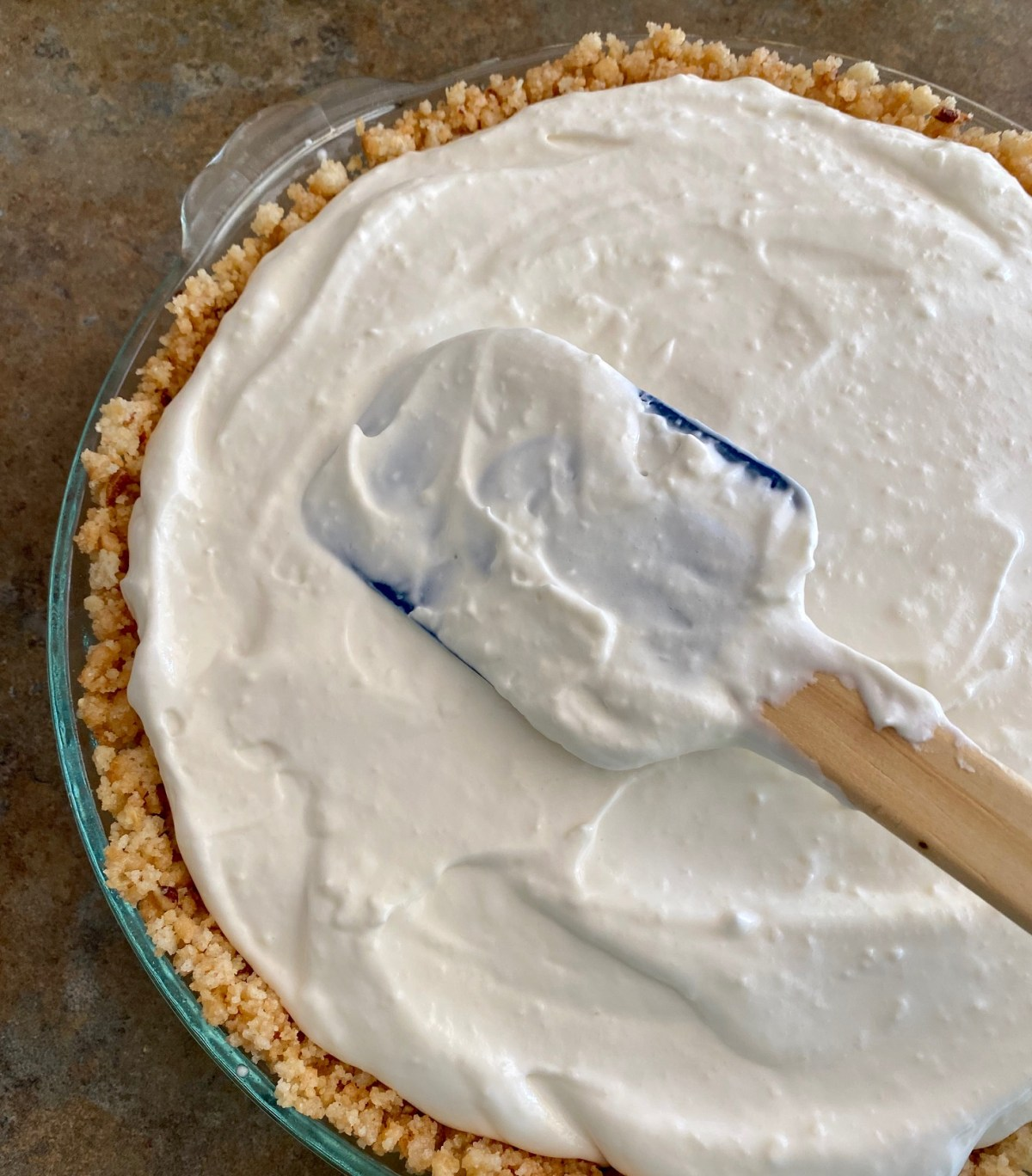 Key lime cream filling is spooned into the cookie crust. #keylimepie #keylimecreampie #creampie #pie #easypierecipes #holidaydessert
