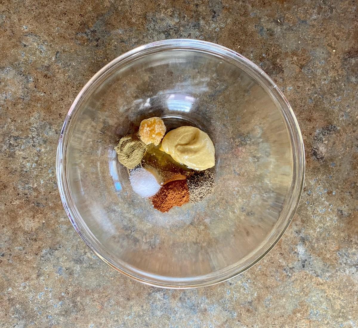 Minced garlic, Dijon mustard, honey, apple pie spice, ground pepper, thyme and salt in a small bowl. #applecideporkchops #porkchoprecipes #bonelessporkchops #dinnerrecipes #30minutesorlessdinner #porkrecipes #applecidergravy
