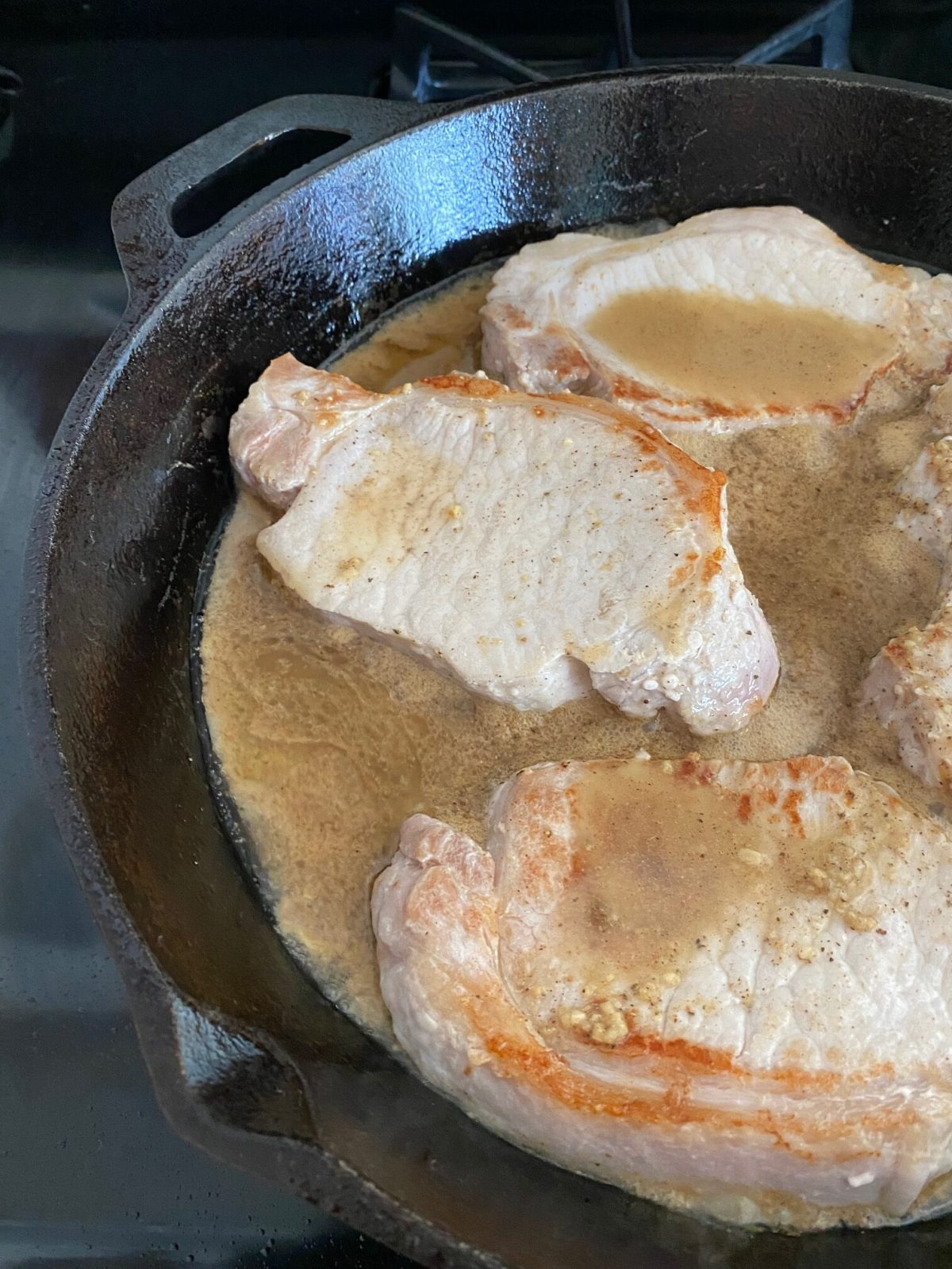 Apple cider mixture poured over the pork chops in a cast iron skillet. #appleciderporkchops #fallrecipes #falldinnerrecipes #coldweatherrecipes #castironskilletrecipes #skilletdinnerrecipes #onepotdinnerrecipes
