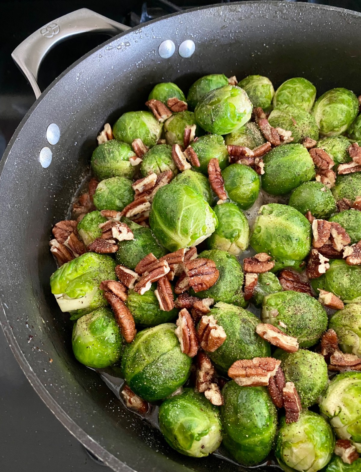 Chicken broth, pecans, maple syrup, salt and pepper are added to the Brussels sprouts skillet. #maplebaconbrusselssprouts #baconbrusselssprouts #maplebrusselssprouts #howtocookbrusselssprouts #cleaneating #dinnerrecipes