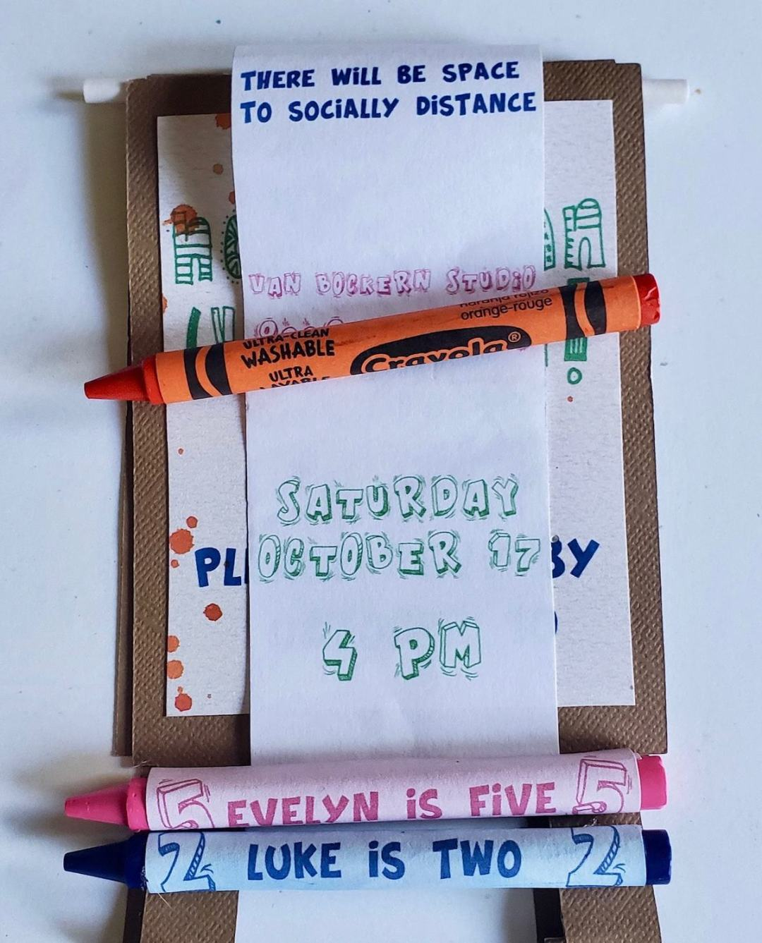 Photo of narrow piece of paper that reads THE VAN BOCKERN SUTDIO; SATURDAY OCTOBER 17, 4 PM; 2 crayons that reads LUKE IS 2, EVELYN IS 4