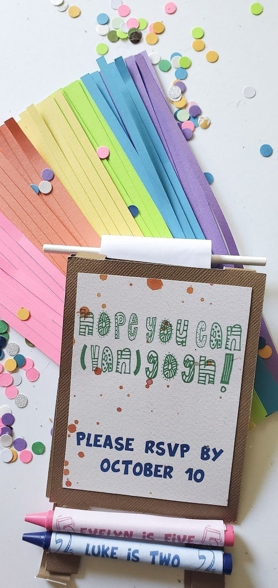 """Invitation laying on top of rainbow tassels and confetti. Invitation reads """"Hope you can van) gogh!; PLEASE RSVP BY OCTOBER 10"""". Pink crayon with label """"EVELYN IS FIVE"""", blue crayon with label """"LUKE IS TWO"""""""