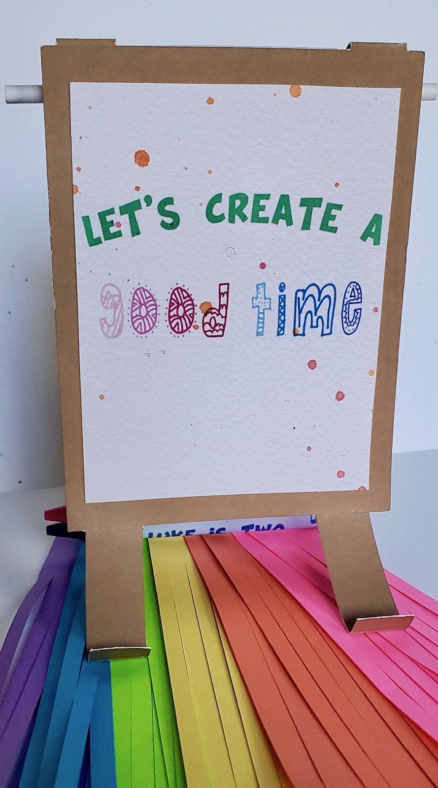 "Photo of rainbow fringe, art easel invitation reading ""LET'S CREATE A GOOD TIME"""