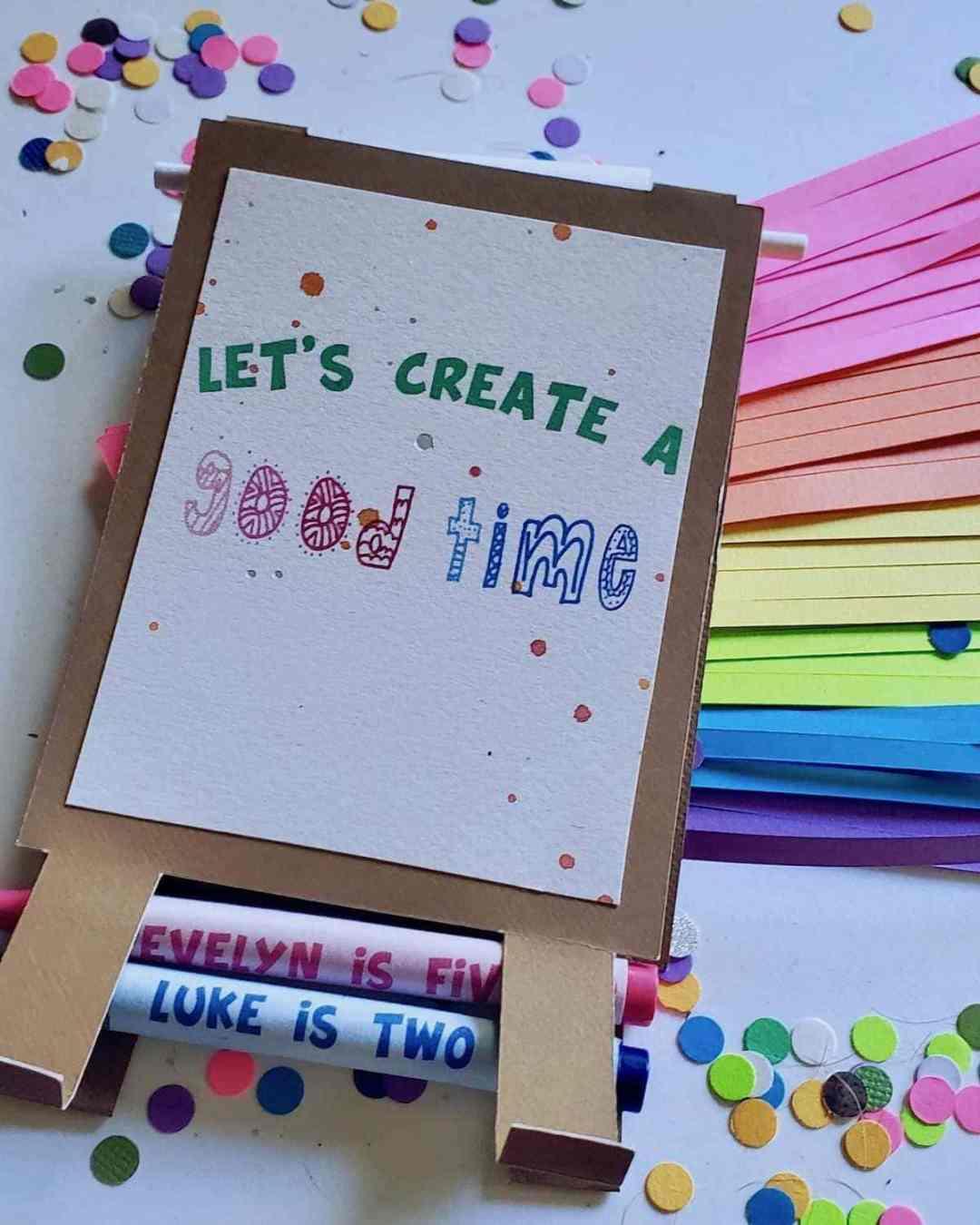 "Photo of rainbow fringe, art easel invitation reading ""LE'TS CREATE A GOOD TIME"""