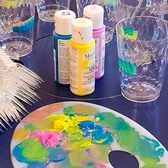 Table with cups that have stripes painted on, yellow, blue and pink bottles of Martha Stewart paint, forks with paint on the handles, painter pallet with blue, yellow, and pink paint smeared on it