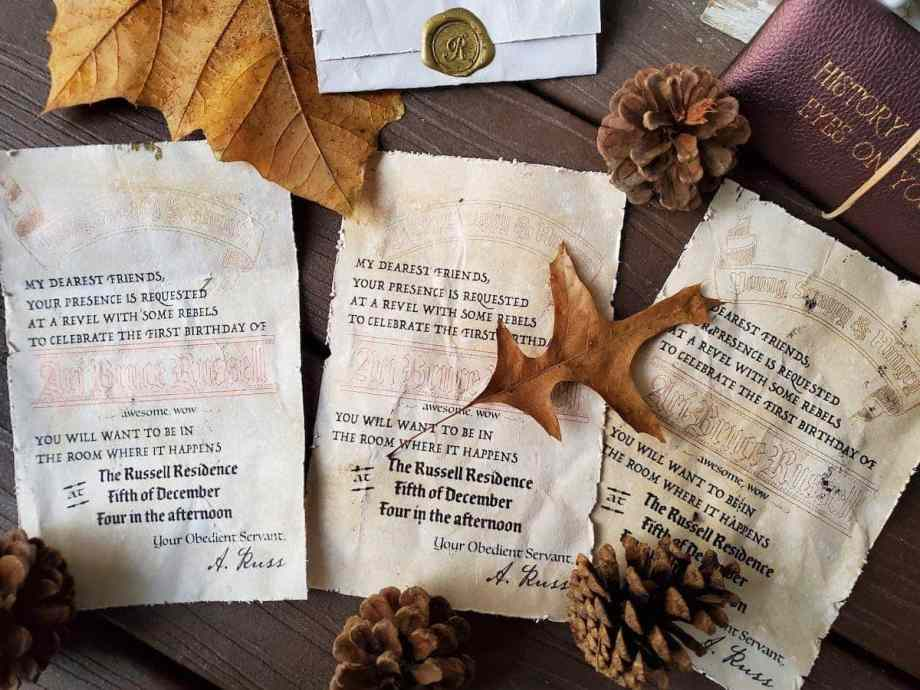 Photo of 3 Hamilton invitations laid out next to each other, folded invitation with gold wax seal with initial R embossed. Leaves and acorns scattered around the invitations
