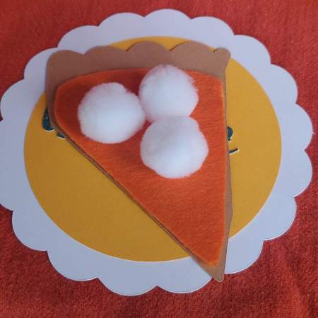 picture of pie made out of cardstock with white pom poms, white scallop and yellow plate, on orange background