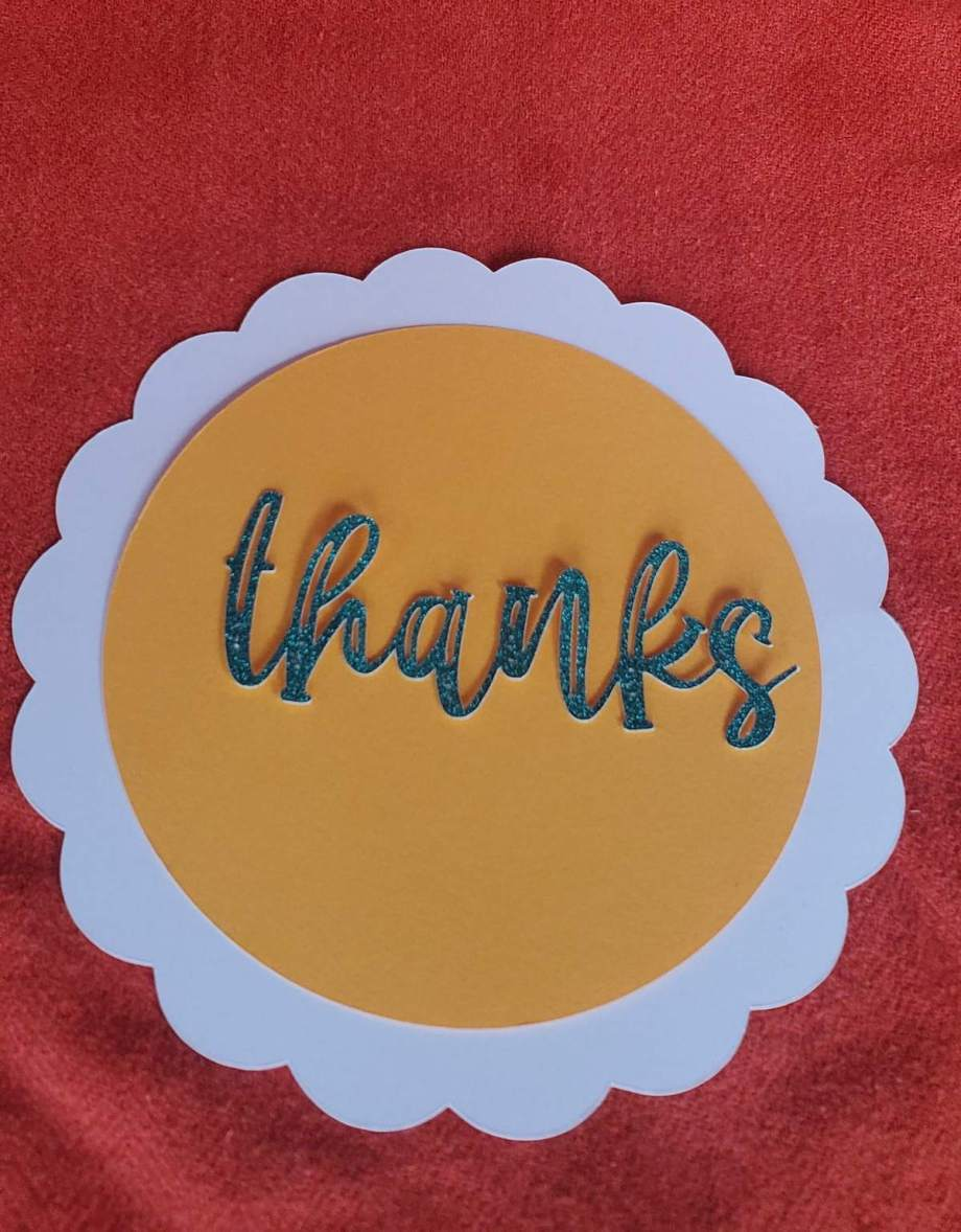 photo of white scallop plate with yellow circle, glittery green cardstock says thanks, all on an orange background