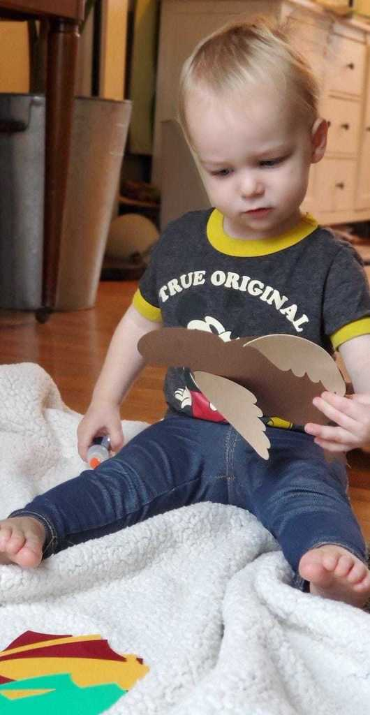 photo of young boy putting together cardstock turkey