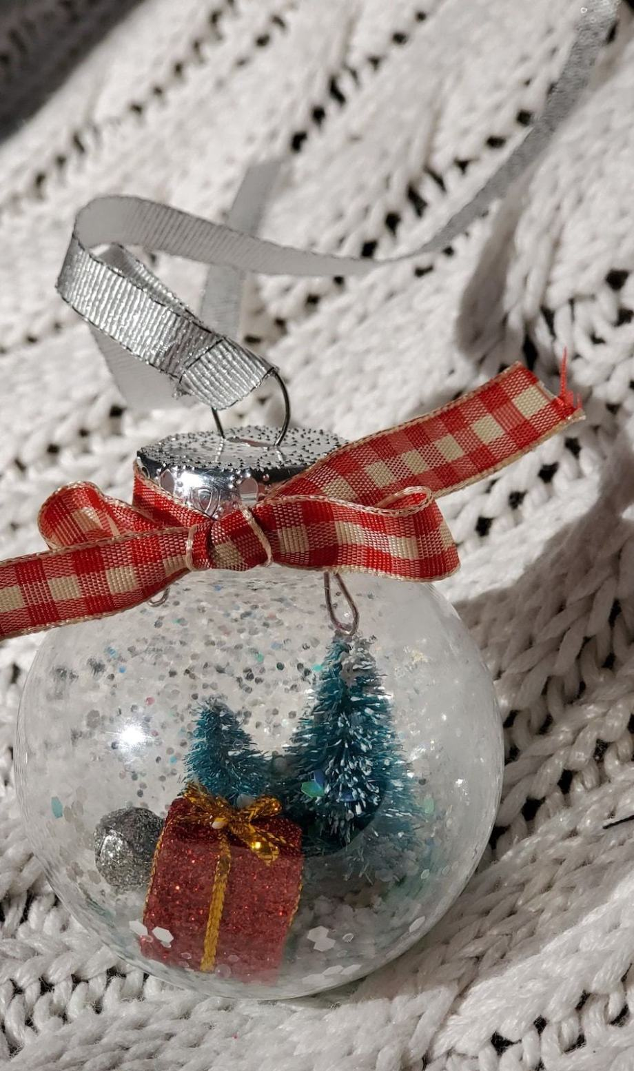 Photo of clear ornament with Christmas trees, present, jingle bells inside.
