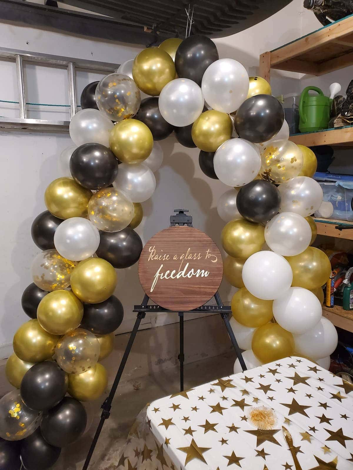 Balloon arch with wood sign RAISE A GLASS TO FREEDOM