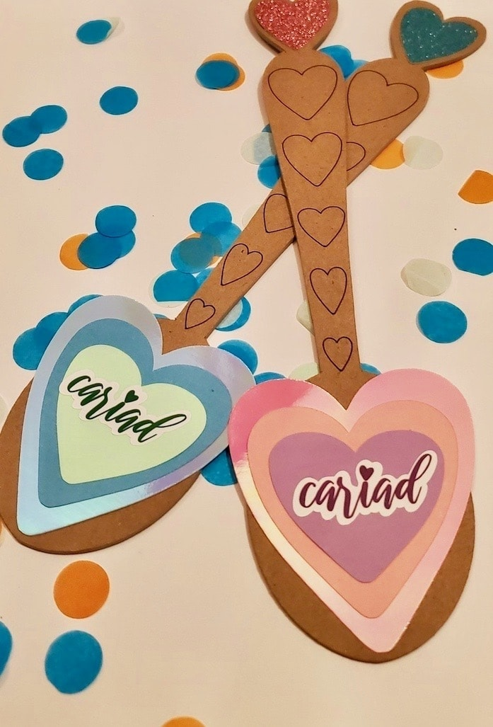 Photo of 2 brown spoons, one with blue hearts, one with pink. Both have stickers that read cariad